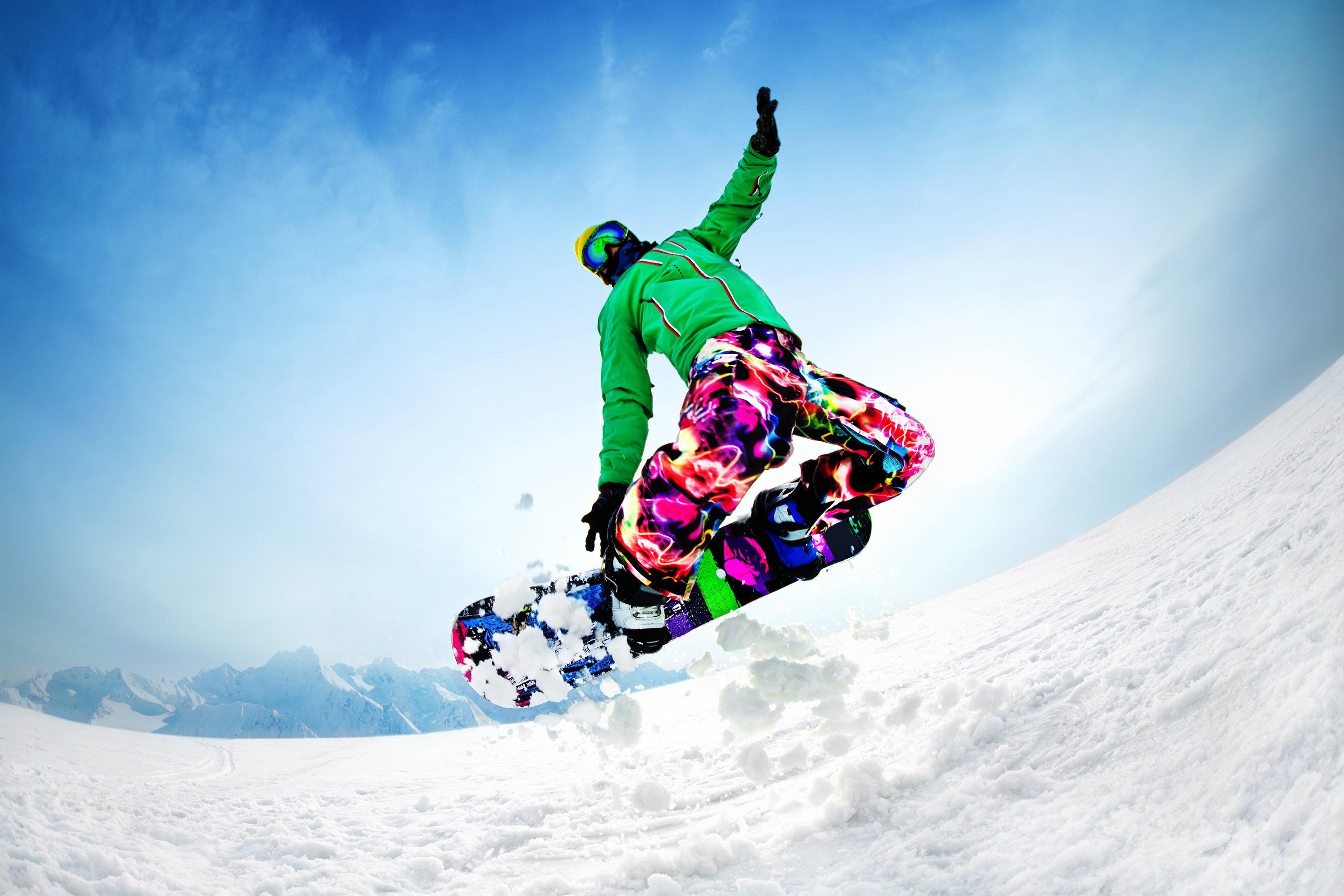 Big snowboarder jumping from the mountain along the road extreme