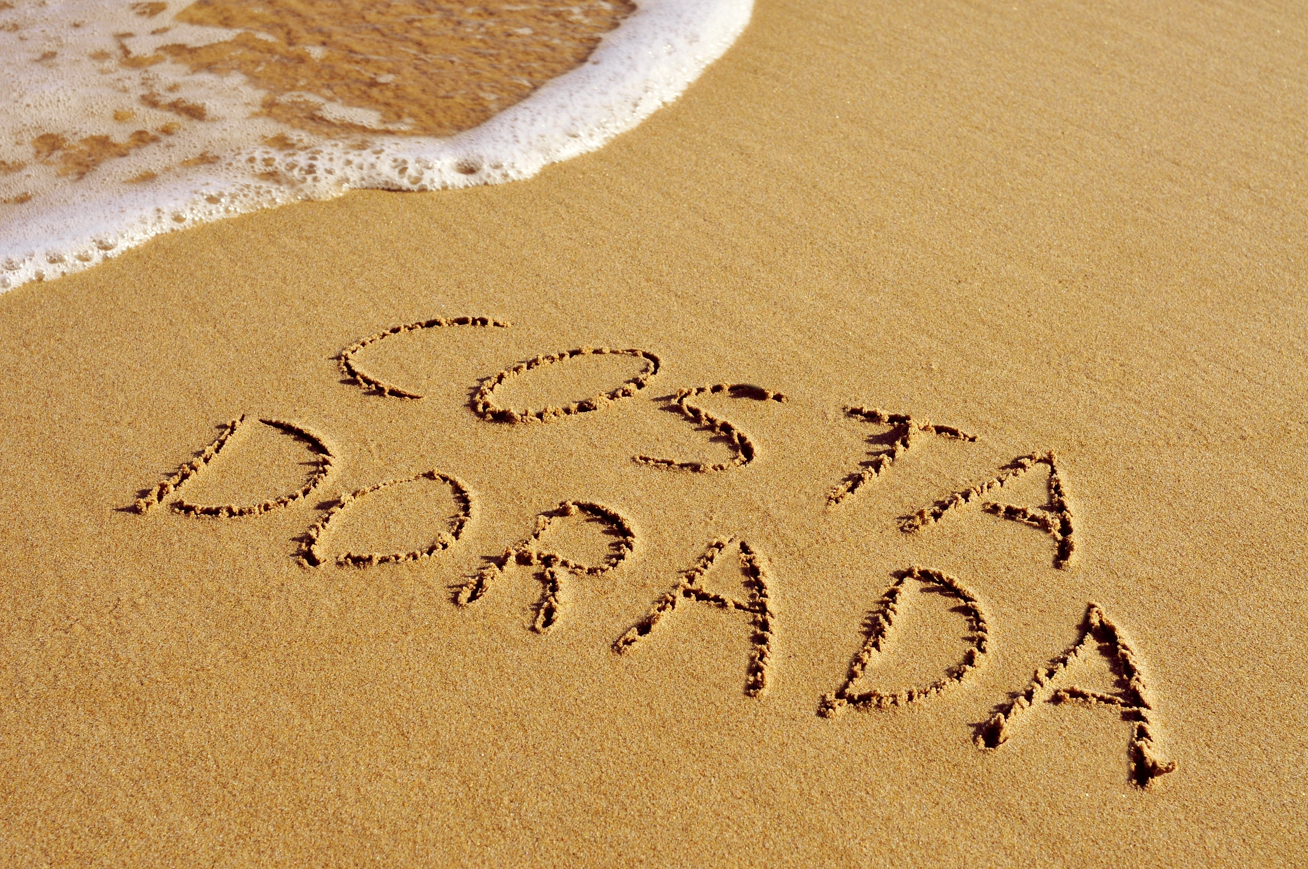 Big costa dorada  the name of an area of the mediterranean coast of spain  written in the sand of a beach